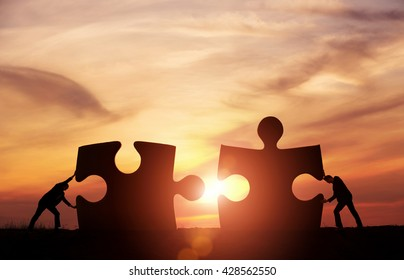 Teamwork concept. Two businessman connecting jigsaw puzzle pieces together with copy space
