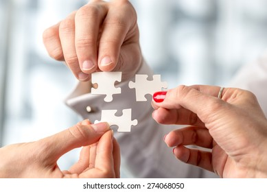Teamwork concept using white puzzle pieces being fitted together by three male and female hands in a challenge, brainstorming and solution concept.