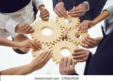 Teamwork concept.Group of businessmen with gears at the table at the workplace in the office.