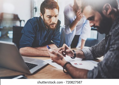 Teamwork concept.Group of three coworkers working together in modern coworking studio.Bearded man using smartphone and talk with partners about new startup project.Horizontal.Blurred background