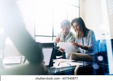Teamwork concept.Young business people working with new startup project.Mobile devices on table,documents and marketing reports.Blurred background,visual effect,flare.Horizontal