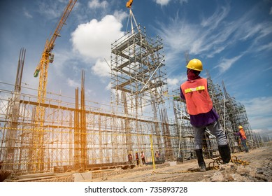 teamwork construction worker installation scaffolding in industrial construction by crane during sunset sky background over time job