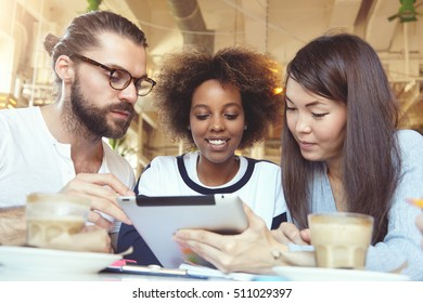 Teamwork and cooperation concept. Three talented young ambitious people brainstorming, having discussion on common project using digital tablet at cafeteria. Multiethnic group working on touch pad