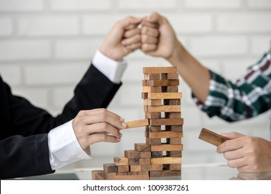 Teamwork and cooperation concept -  young business hands building a structure of wooden blocks . teamwork business signs on rustic table surface.