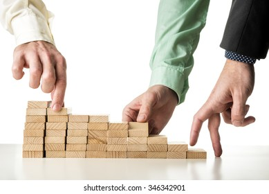 Teamwork and cooperation - two male hands assembling strong foundation of wooden pegs for the third hand to walk its fingers up the steps toward success.