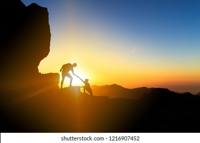 Teamwork couple helping hand trust help silhouette in mountains, sunset. Team of climbers man and woman hikers, help each other on top of mountain, climbing together, inspiring sunset on Gran Canaria
