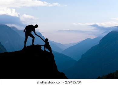 Teamwork couple helping hand trust assistance silhouette in mountains, sunset. Team of climbers man and woman hiker, help each other on top of mountain, beautiful landscape in Himalayas Nepal