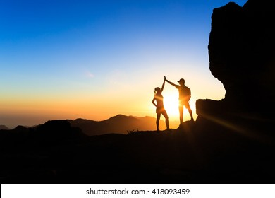 Teamwork couple helping hand trust help, silhouette success in mountains. Team of climbers man and woman. Hikers celebrate with hands up, help each other on top of mountain, happy climbing together.