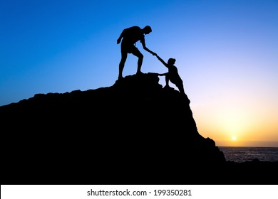 Teamwork couple hiking help each other trust assistance silhouette in mountains, sunset. Teamwork Male and woman hiker helping each other on top of mountain climbing team, beautiful sunset landscape.
