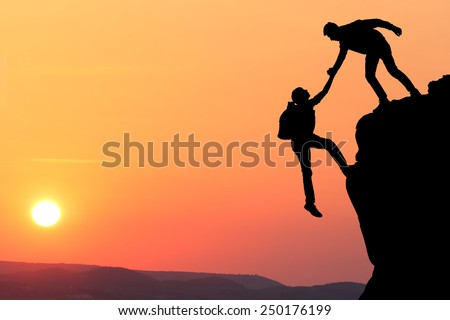Teamwork couple hiking help each other trust assistance silhouette in mountains, sunset. Teamwork of two men hiker helping each other on top of mountain climbing team, beautiful sunset landscape.
