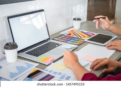 Teamwork of creative designers working on new project and choose color swatch samples for selection coloring on digital graphic tablet with work tools and equipment at workplace.