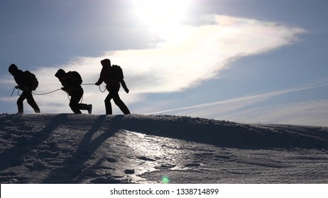 teamwork desire to win. Climbers on a rope help a friend climb to the top of the hill. Silhouette of travelers in winter on a hill in the bright rays of sun. concept of sports tourism.