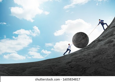 Teamwork example with business people pushing stone to top