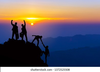 Teamwork friendship hiking help each other trust assistance silhouette in mountains, sunrise. Teamwork of four men hiker helping each other on top of mountain climbing team beautiful sunrise landscape