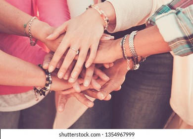 Teamwork and friendship together concept with hands put on hands - women power day for work and friends - caucasian people team in vintage filter colors