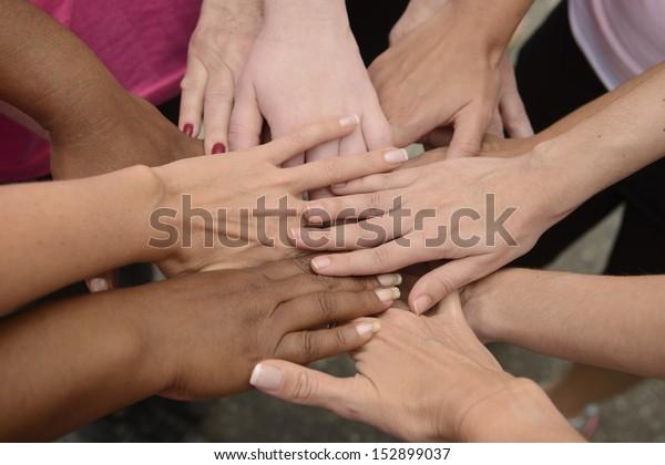 Teamwork: group putting hands together