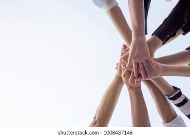 Teamwork group of young people putting their hands together for showing unity .