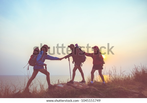 Teamwork hiker women helping her friend climb up the last section of sunset in mountains.  Traveler teamwork in outdoor lifestyle adventure and camping.  Travel Concept.