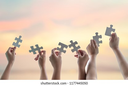 Teamwork idea brainstorming, team partnership connection for problem solving, finding solution in hope concept with jigsaw puzzle pieces in school children or student kids's hands