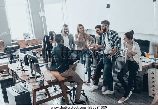 Teamwork is a key to success.  Full length top view of young business people in smart casual wear talking and smiling while having a brainstorm meeting in office