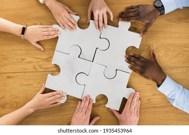 Teamwork Meeting Hands Solving Jigsaw Puzzle. Overhead View