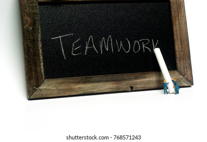 "Teamwork - Miniature construction worker figurines posed as if writing ""Teamwork"" on a chalkboard."