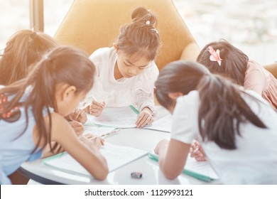 Teamwork. Nice little kids making notes and studying together while working in a group