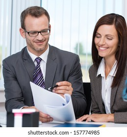 Teamwork in the office with a business man and woman sitting close together at a desk discussing a paper document with smiling faces