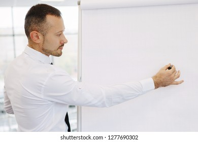 Teamwork of office staff. Businessman coach in a white shirt and tie, standing near the flipchart, explains the schedule of tasks for the future. Business training. Personal growth.