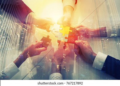 Teamwork of partners. Concept of integration and startup with puzzle pieces. double exposure