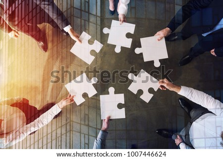 Teamwork of partners. Concept of integration and startup with puzzle pieces