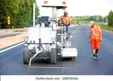 Teamwork: Pavement Asphalt Road Marking Paint and Striping with Thermoplastic Spray Applicator Machine during highway construction works