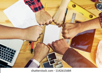 teamwork and people concept - close up of international students hands making fist bump gesture. hands teamwork in meting room office.