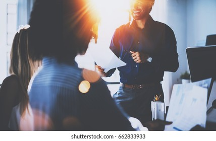 Teamwork people concept.Young team of coworkers making great business discussion in modern coworking office.Hispanic businessman talking with partners.Horizontal, blurred background, flares