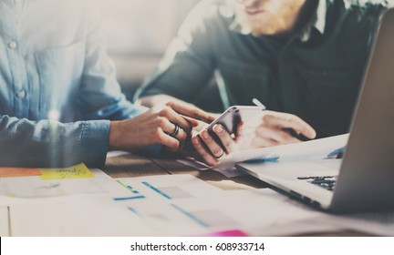 Teamwork process concept.Young coworkers working with new startup project at the office.Girl pointing finger on screen of smartphone and show it to the partner.Horizontal, blurred