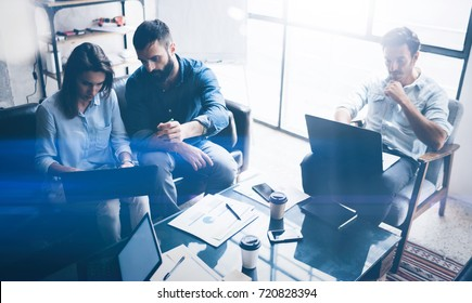 Teamwork process.Young coworkers work with new startup project in office.Modern laptop on table, papers, documents.Horizontal, blurred background