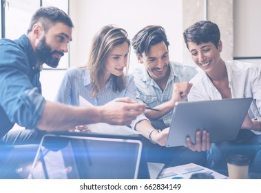 Teamwork process.Young entrepreneur work with new startup project in office.Woman holding touch pad in hands,bearded man pointing to screen.Horizontal, blurred, flare.