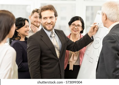 Teamwork in progress. Handsome confident mature man writing on a flipchart during presentation for his business team corporate success brainstorming teamwork communication office busy leader concept