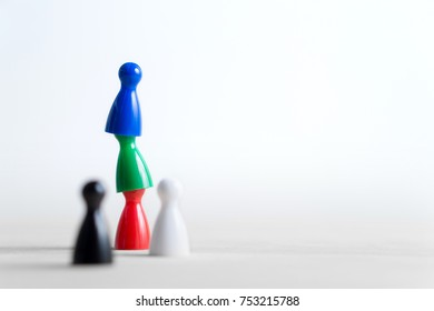 Teamwork, reaching goals, working together and success concept. Cooperation, leadership, achievement and support. Colorful board game pawns on each other. Negative copy space.