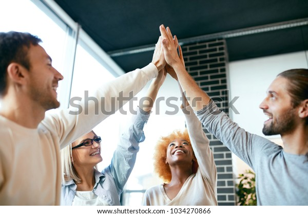 Teamwork. Smiling People Putting Hands Together, Celebrating Successful Work. Group Of Happy Young Men And Women Having Fun Holding Hands Together In Office. High Quality