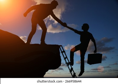 Teamwork of two men helping each other on top of mountain a career climbing team, concept of career ladder and teamwork