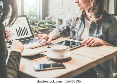 Teamwork. Two young business woman sitting at table in coffee shop, look at chart on laptop screen and develop business plan. Business meeting in restaurant. On table tablet PC,cup of coffee,notebook.