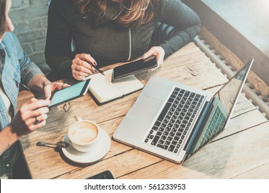 Teamwork. Two young businesswomen sitting at table in coffee shop, look at your smartphone screen and discuss business strategy. Girl taking notes in notebook. On table laptop and cup of coffee.