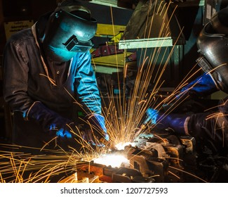 Teamwork worker with protective mask welding metal