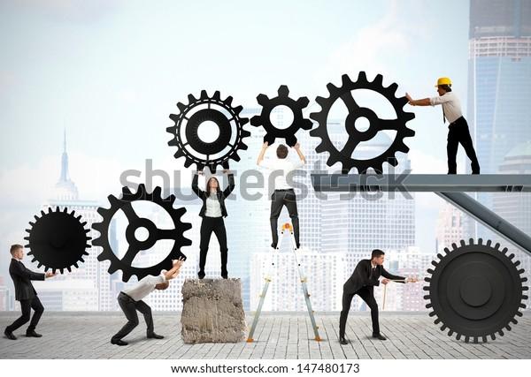 Teamwork arbeitet zusammen, um ein Getriebe zu bauen