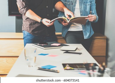 Teamwork. Young business woman and businessman standing at table and look in directory. Designer advises clients on selection of finishing materials. Man is pointing to page in book.Students learning.