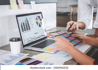 Teamwork of young creative designers working on project together and choose color swatch samples for selection coloring on digital graphic tablet and equipment at workplace.