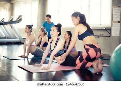 Teamwork of young women and young man doing yoga exercises in gym,concept healthy life fitness for slim