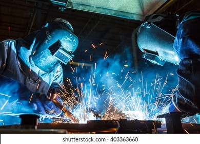 Teamworker with protective mask welding metal
