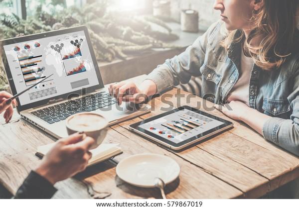 團隊合作,兩位年輕的商務女性坐在桌上,喝咖啡和在線工作。第一位女孩在電腦屏幕上顯示筆圖表和圖表。
